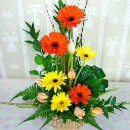 Pink roses with orange and yellow Geraberas in a Flower Basket